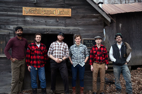 """Six men in plaid shirts stand in front of a sugar shack. A sign behind them reads """"West Hill Sugar Orchard""""."""